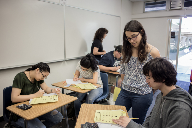 Power Study Program tutor Valeria Zepeda (standing, right) helps students solve math problems in Professor Myriam Moody's intermediate algebra class.
